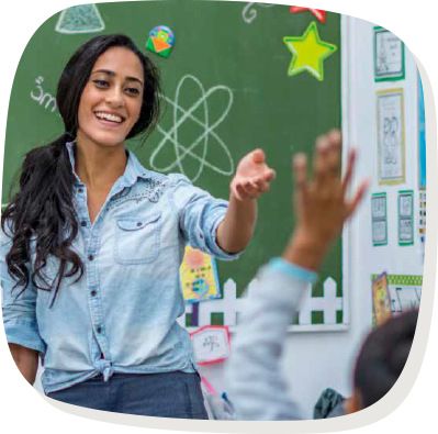 Teacher in front of class with childs hand in the air